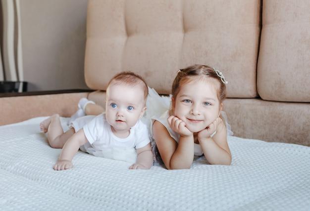 Две маленькие девочки в белых платьях, сестры играют дома, на диване