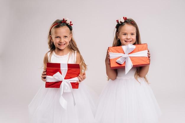 白い背景の笑顔でクリスマスプレゼントと白いドレスを着た2人の少女