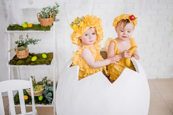 Two little girls in yellow dresses sit in an egg in the studio
