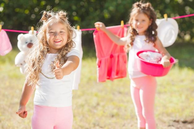 Two little girls laundring. sisters doing housework