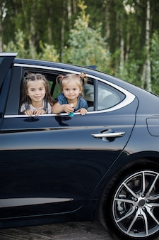 Two little girls look through a car window.