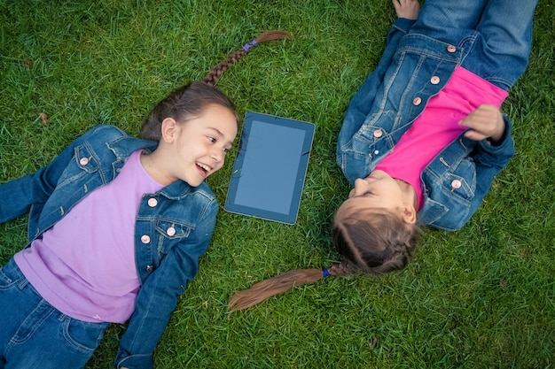 Two little girls lying face to face on grass and looking at tablet