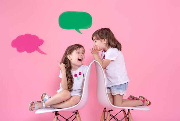 Две маленькие девочки на цветной стене с речевыми иконами