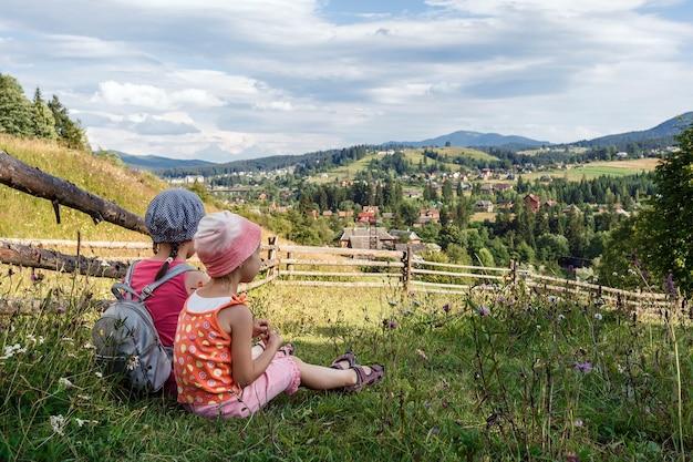 산비탈에 있는 두 소녀는 산의 풍경에 감탄한다
