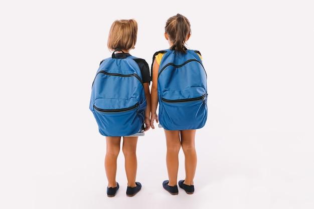 2人の少女、1人はブロンドの髪、もう1人は黒髪で、青いデニムのオーバーオールに身を包み、バックパックを背負って、白い背景に背中を向けて学校に戻る準備ができています。