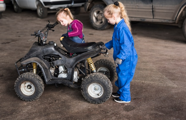 Two little girls in overalls inspecting quad bike