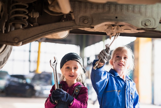 Two little girls in overalls repairing car with spanners