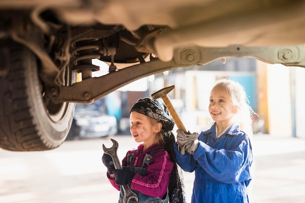 Two little girls in overalls standing with tools