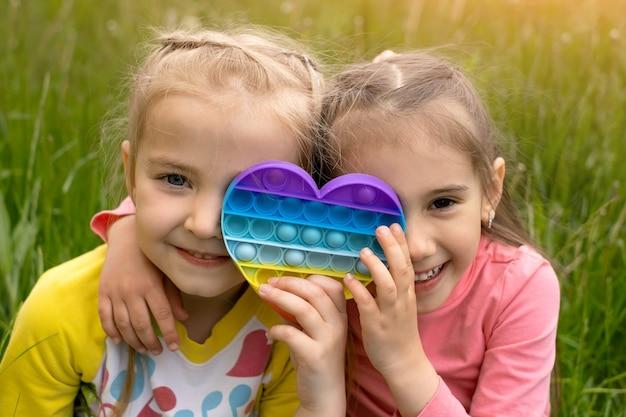 두 명의 어린 소녀가 현대적인 하트 모양의 포핏 장난감을 가지고 노는 모습