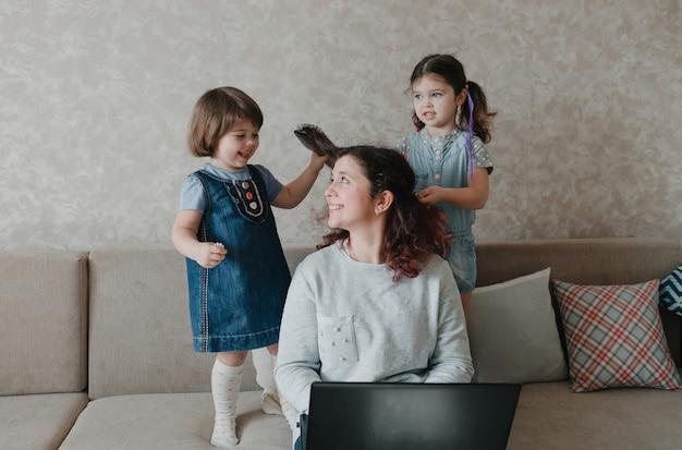 二人の少女は母親と遊んだり、髪をしたり、髪をとかしたりします。思いやりのある母親