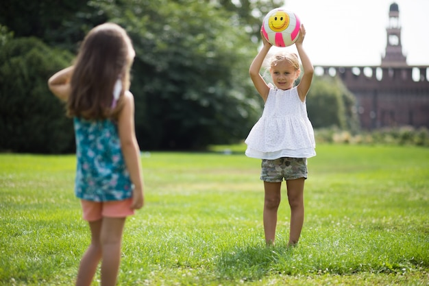 Two little girls playing with the ball
