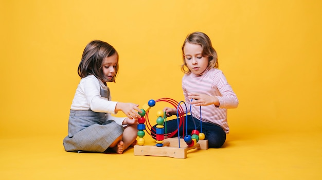 Two little girls playing with toys on a yellow isolated background
