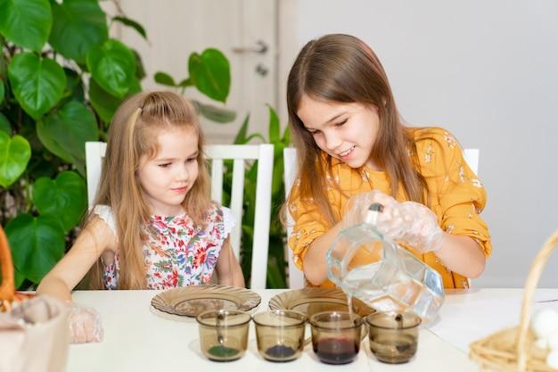 Две маленькие девочки наливают воду в стаканы с краской, чтобы украсить яйца. пасхальные семейные традиции. детское творчество