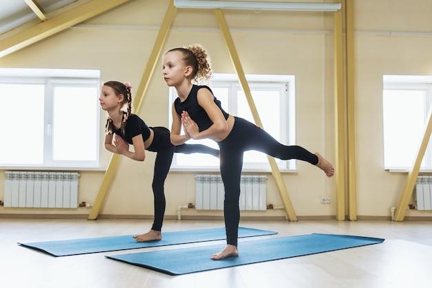 Virabhadrasana 운동 전사를 수행하는 요가 연습 두 어린 소녀 스포츠웨어에서 운동하는 3 명의 아이들 포즈