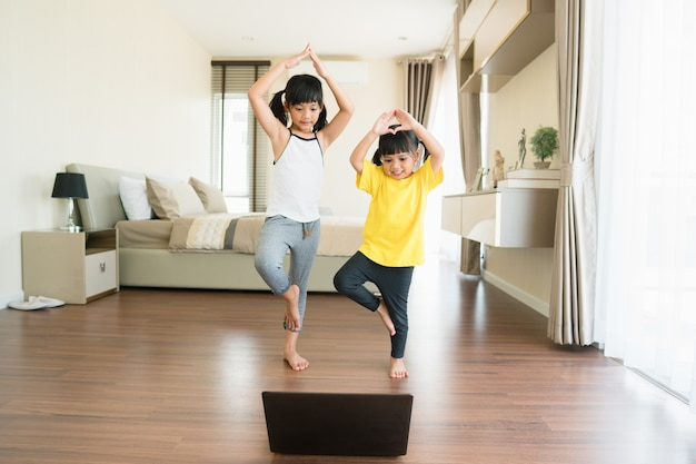 Two little girls practicing yoga, stretching, fitness by video on notebook.
