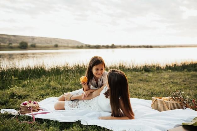 2人の少女、かなり小さな姉妹が自然の中で格子縞の上に座っています