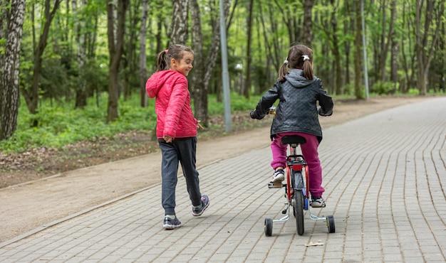 Две маленькие девочки катаются на велосипеде в парке весной.