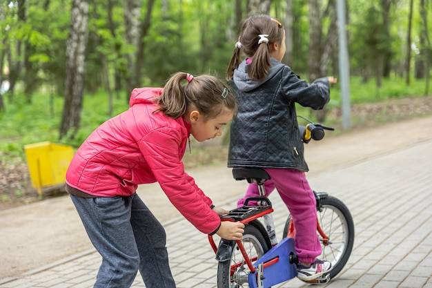 Two little girls ride a bike in the park in spring.
