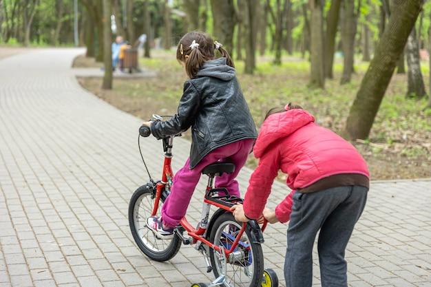 Due bambine vanno in bicicletta nel parco in primavera