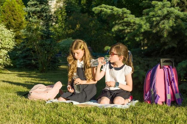 Two little girls schoolchildren drink water