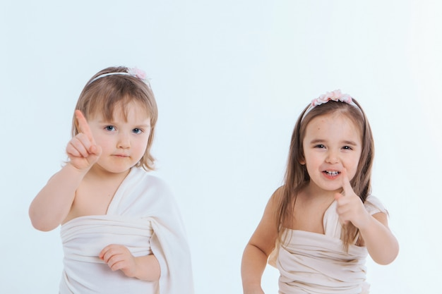 Two little girls shake their fingers at a white background. children raise each other. the concept of education , childhood, and sisterhood. copy space