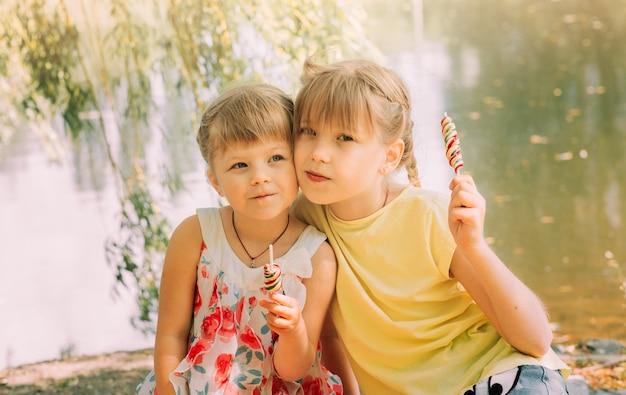 여름에 공원에서 막대 사탕을 들고 두 어린 소녀 자매