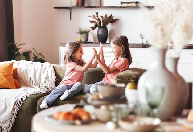 二人の妹が居間のソファで一緒に遊んで楽しんでいます