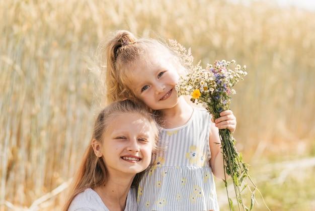 두 명의 어린 소녀 자매가 여름에 포옹하고 꽃을 모은다