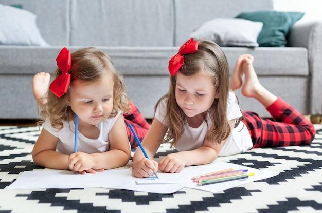두 소녀 자매는 집 바닥에 누워 종이에 색연필로 그립니다.
