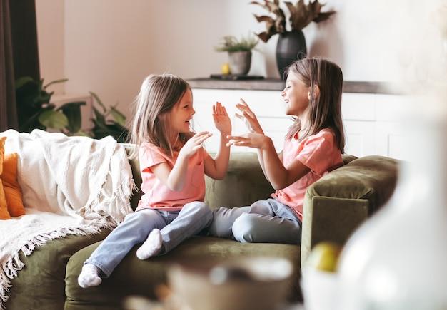 二人の妹が居間のソファで楽しく遊んでいます。子供たちは一緒に楽しく時間を過ごします