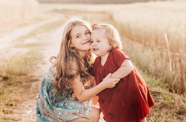 Две маленькие девочки-сестры играют на пшеничном поле