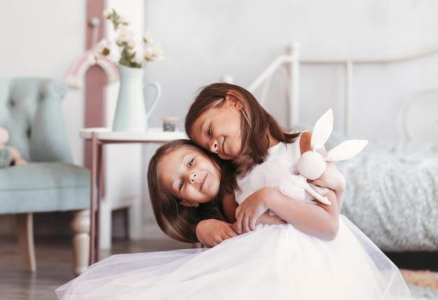 2人の小さな女の子の姉妹は明るい部屋でお互いに遊んでいます。一緒に幸せな子供たち。シンブリングが大好き