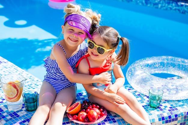 2人の少女が夏にプールのそばに座ってサングラスをかけ、レモネードを飲みます