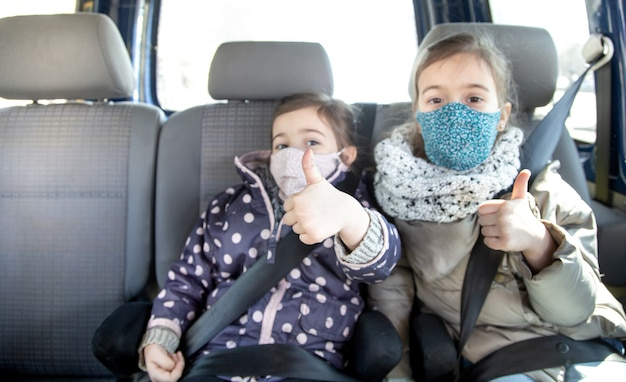 Two little girls sit in a car in the back seat, wearing masks during the pandemic