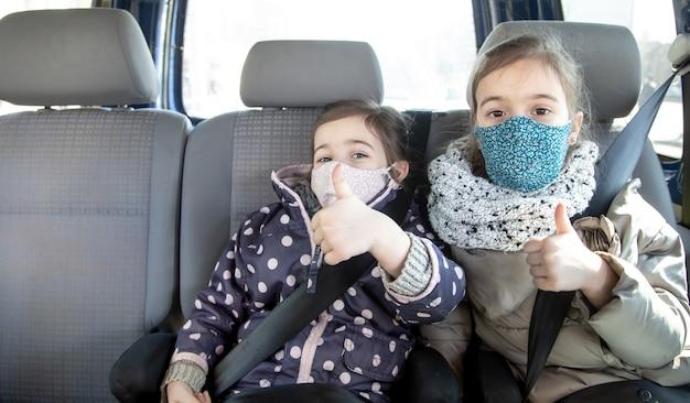 パンデミックの間、2人の少女が後部座席の車に座ってマスクを着用します。