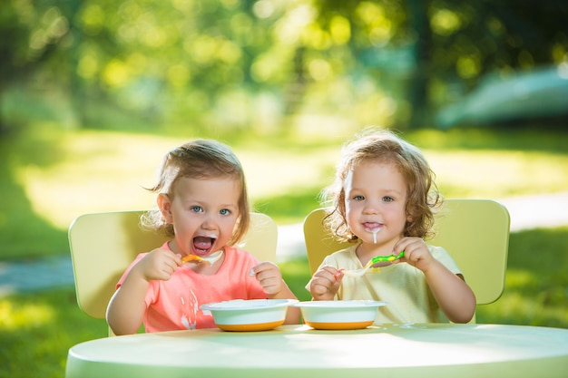 두 소녀는 테이블에 앉아 및 녹색 잔디밭에 대해 함께 먹는