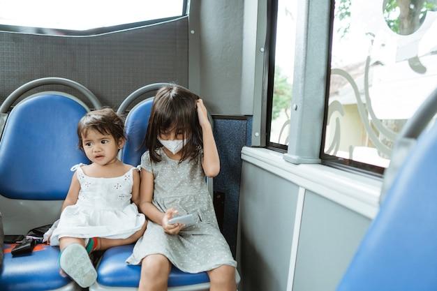 여행하는 동안 버스에서 휴대 전화로 벤치에 앉아 두 어린 소녀