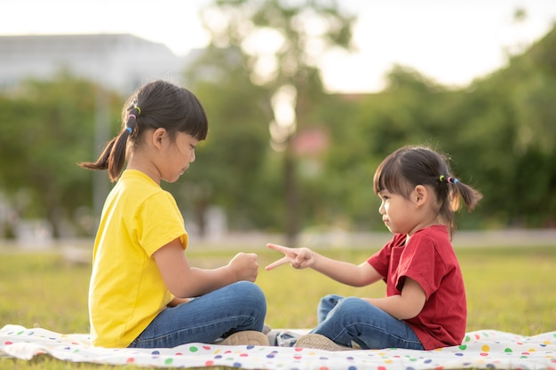 공원의 잔디에 앉아 가위바위보 게임을 하는 어린 소녀 두 명