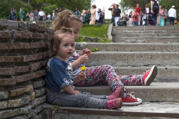Две маленькие девочки, сидящие на ступеньках снаружи, концепция отдыха детей