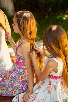 屋外に座って、公園でヘアスタイルをしている 2 人の少女