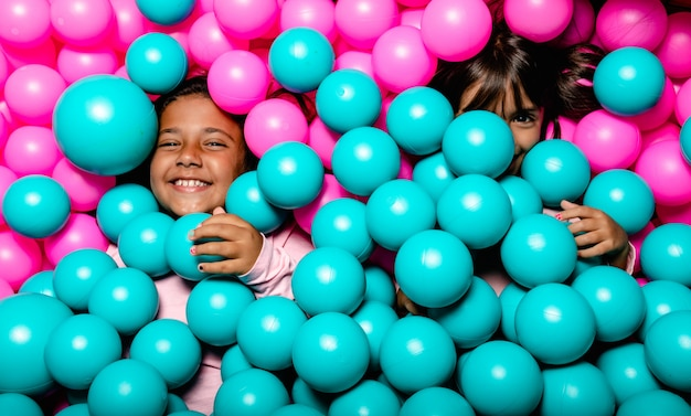 Two little girls smiling and playing at blue and pink ball pool
