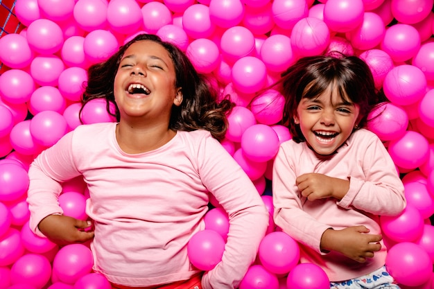 Two little girls smiling and playing at pink ball pool