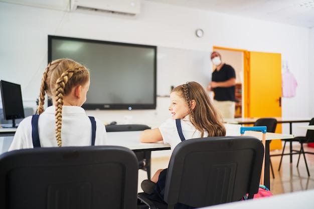 교사가 그들을 볼 때 서로 웃는 두 어린 소녀