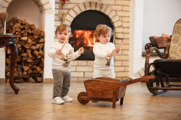 The two little girls standing at home against fireplace