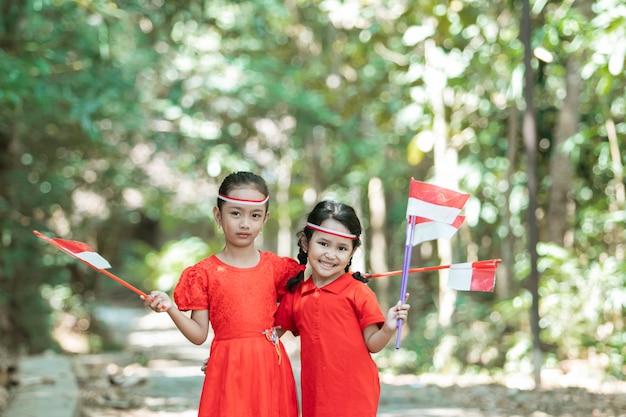 Две маленькие девочки, стоящие в красной рубашке и красно-белом атрибуте, держат красно-белые флаги