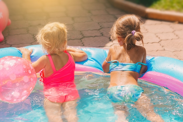 Two little girls in swimsuits play in the childrens pool in the yard