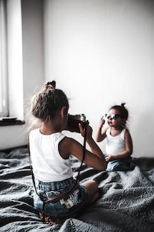Две маленькие девочки фотографируют друг друга. маленькие модницы