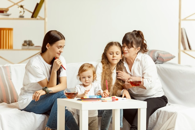 두 어린 소녀 그들의 매력적인 젊은 어머니와 소파에 앉아 집에서 함께 시간을 보내는 매력적인 할머니. 여성 세대. 세계 여성의 날. 해피 어머니의 날.