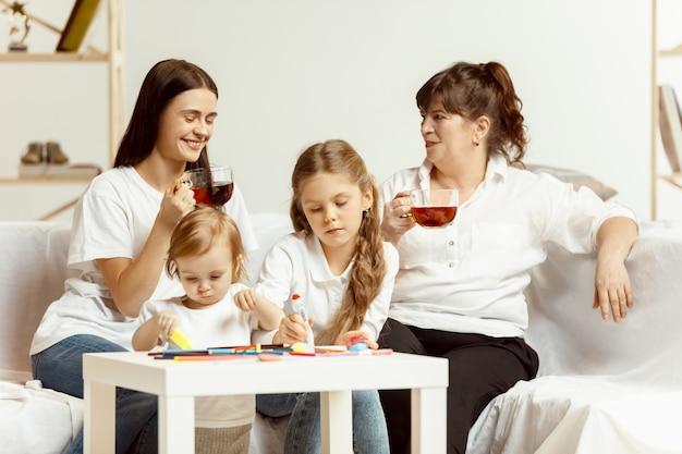 魅力的な若い母親と魅力的な祖母がソファーに座って、家で一緒に時間を過ごす2人の少女。女性の世代。国際婦人デー。母の日おめでとう。