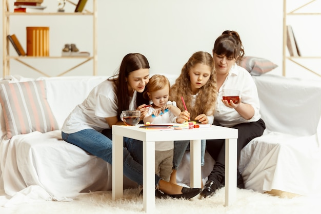 Two little girls their attractive young mother and their charming grandmother sitting on sofa and spending time together at home. generation of women. international women's day. happy mother's day.